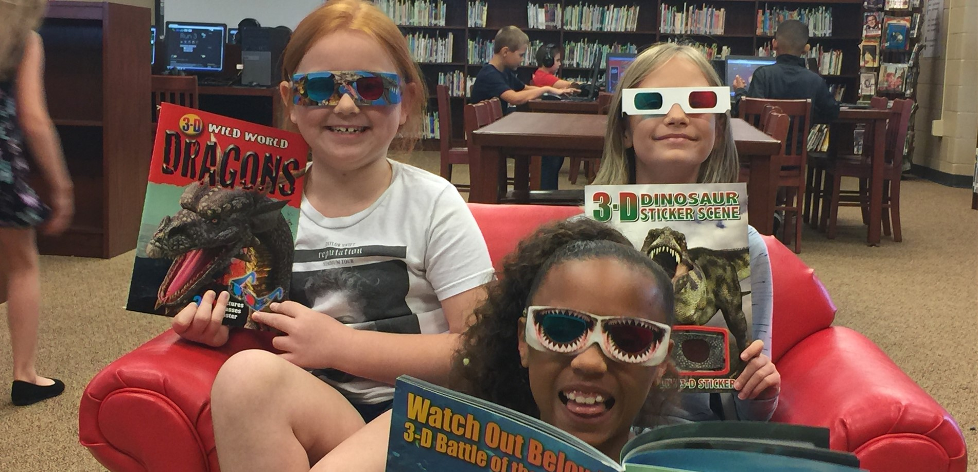 Students read 3-D books in the media center.