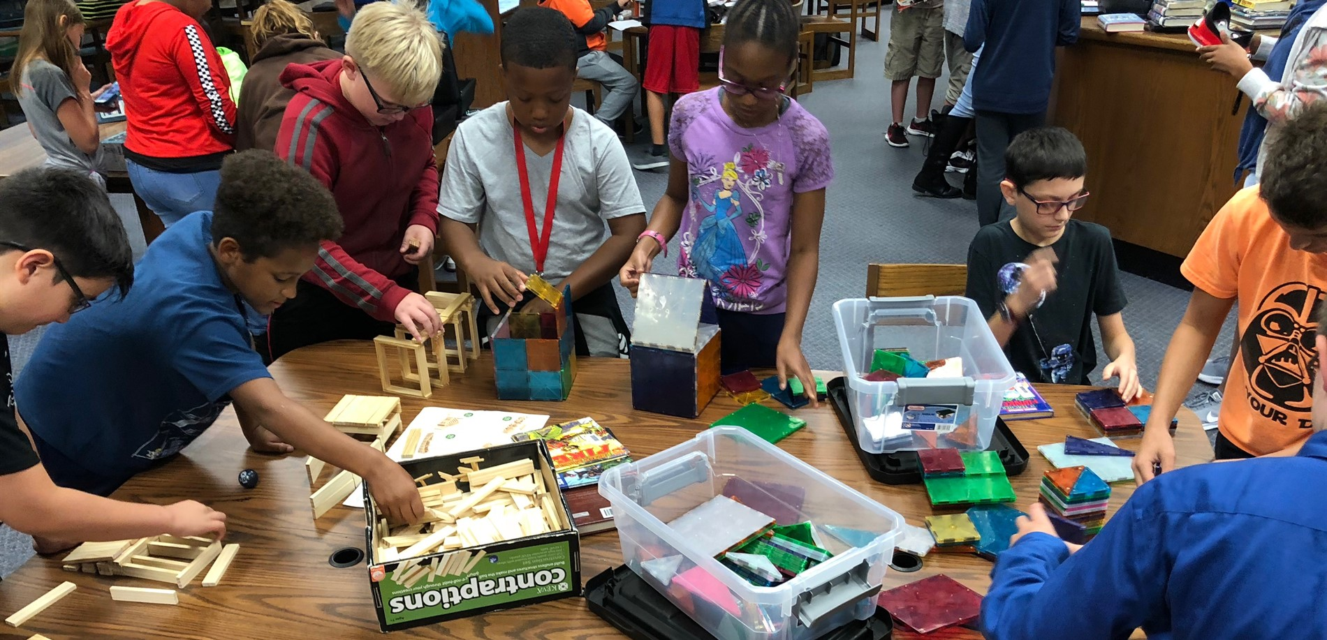 Students are in the JTA library media center using KEVA planks and Mangatiles to engineer buildings.