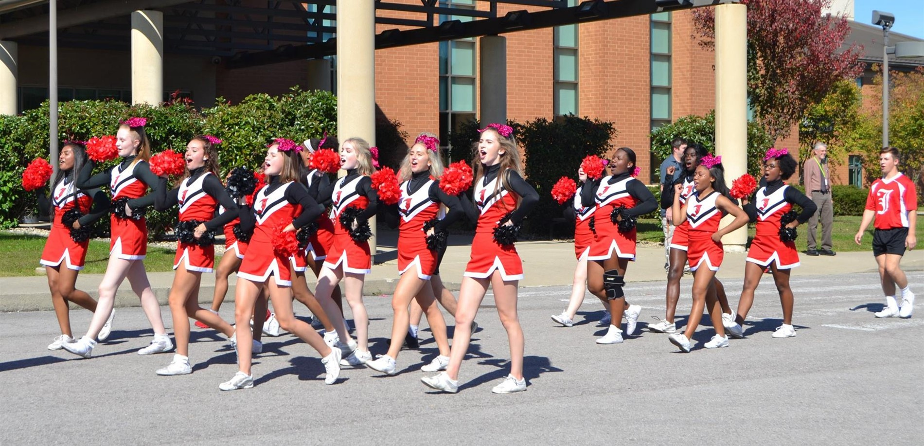 John Hardin High School cheerleaders lead the Homecoming Parade in front of school.