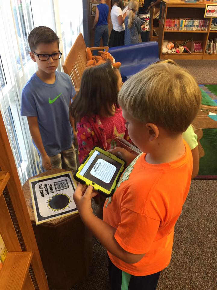 Students use ipads to scan QR codes with info on eclipese