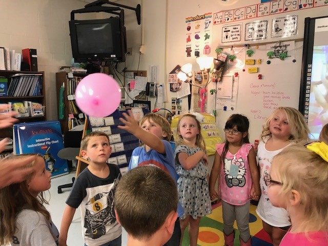Kindergarten students work together to keep a balloon off the ground.